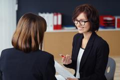 Manager Talking to her Subordinate in the Office Stock Photos