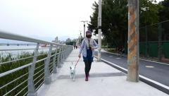Riverside promenade, pedestrian walkway, women walk dog, dusk time Stock Footage