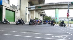 Scooters traffic on junction at dam gate to Tamsui riverside park and roads Stock Footage