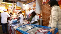 Women put sausages from fresh meat on tray, night city market booth Stock Footage