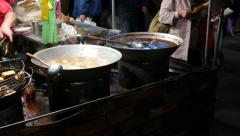 Two wok with boiling broth, open kitchen restaurant on night market Stock Footage