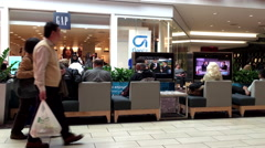 Shopper sitting rest area and watching TV inside Coquitlam Center shopping mall Stock Footage