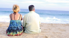 An older couple sitting on the beach and watching the waves - stock footage