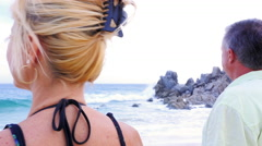An older couple looking out at the ocean, close up from behind - stock footage