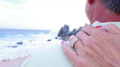 Close up of a woman's hand on her husband's shoulder at the beach - stock footage