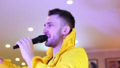 Showman in yellow fashionable suit speaks in a microphone. - stock footage