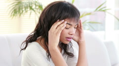 Stressed woman holding her head on couch Stock Footage