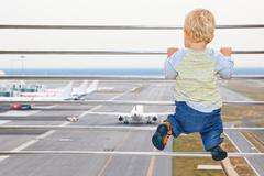 Baby boy in airport transit hall looking at airplane - stock photo