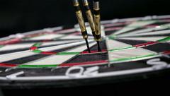 Stock Video Footage of Close up of three darts hitting triple twenty on a dart board, 4K
