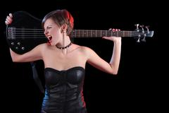 Sexy girl in leather clothes with bass guitar. punk rocker - stock photo