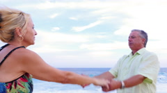 Close up of an older couple dancing on the beach Stock Footage