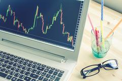 Stock or Forex Graph in Laptop Screen on Blue Vintage Style Stock Photos