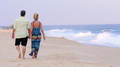 View from behind of an older couple holding hands Stock Footage
