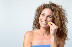 woman cleaning her teeth with an interdental brush - stock photo
