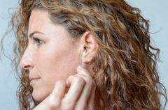 woman cleaning her ear with a cotton swab - stock photo