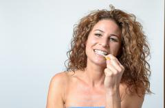 Woman cleaning her teeth with an interdental brush Stock Photos
