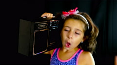 Cute little girl singing and dancing with an old cassette tape on her shoulder Stock Footage
