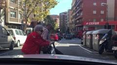 Old lady in read coat walking across in front of car windshield Stock Footage