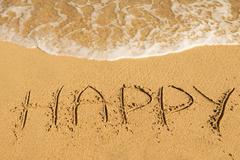Stock Photo of Happy  message on the sand