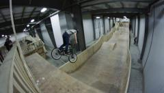 Wide angle shot of BMX rider going really high on a ramp setup Stock Footage