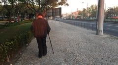 Old man walking alone with walking stick on a pavement near freeway Stock Footage