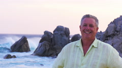 Portait of an older man standing on the beach - stock footage