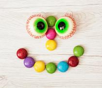 Smiling face of smarties and chewing gums in the form of eyes - stock photo