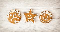 Three tasty gingerbread smiley faces, Christmas symbol Stock Photos