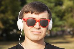 Man with white headphones and sunglasses Stock Photos