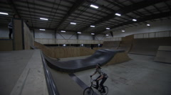 BMX Rider doing Acrobatic Impossibilities in an indoor skateboard park Stock Footage