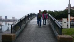 Walk to and over pedestrian bridge in dusk, Tiamsu river waterfront promenade Stock Footage