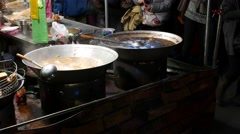 Open kitchen place at night market, close view to wok full of boiling broth Stock Footage