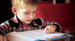 boy learning to read a book - stock footage