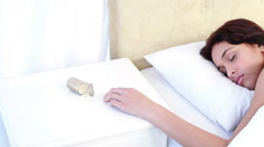 Woman sleeping in bed by spilt bottle of pills on table - stock footage