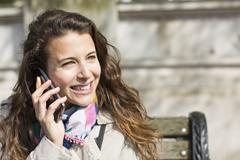 Attractive young woman smiling as she talks on her phone outside, sat on a bench Stock Photos