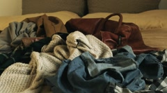 Clothes in disorder with vintage leather suitcase Stock Footage