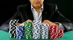 A gambler at a poker table peeks at his cards €˜and tosses them to the camera Stock Footage