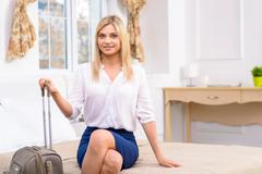 Girl with luggage in her hotel suite - stock photo
