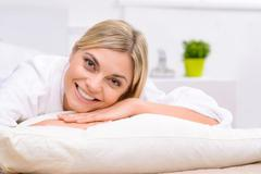 Smiling young woman lying in bed - stock photo