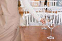 Waitress is putting water glasses on the tables - stock photo