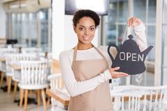 Smiling waitress holding an opening sign Stock Photos