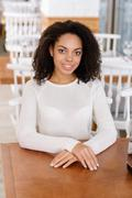 Young woman sitting at the table Stock Photos