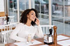 Cheerful young woman making phone call - stock photo