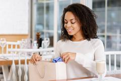 Young woman checking her shopping bag - stock photo