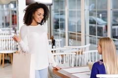 Young woman meets her friend at the restaurant Stock Photos