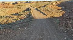 POV-dirt road in desert morning light from shadow into sunlight Stock Footage