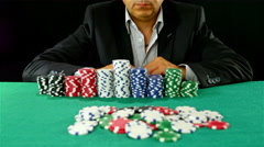 Stock Video Footage of A gambler at a poker table wins and makes a challenge gesture to the camera