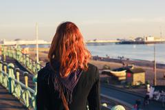 Woman admiring the sea at sunset - stock photo