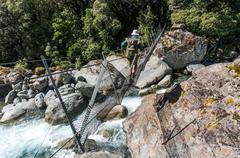 Man crossing footbridge, Arthur's Pass National Park, New Zealand - stock photo