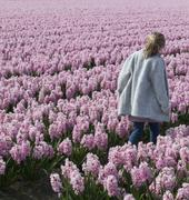 Girl walking through a field of pink hyacinth flowers Stock Photos